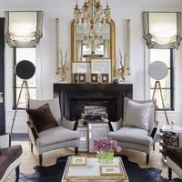 The living room armchairs, covered in a Rogers &amp&#x3B; Goffigon stripe, and cocktail tables are by Megan Winters Collection, the vintage chandelier is by Baccarat, the mirror was found in Paris, and the floor lamps are made from antique surveyor tripods&#x3B; the linen wallcovering is by Ralph Lauren Home.
