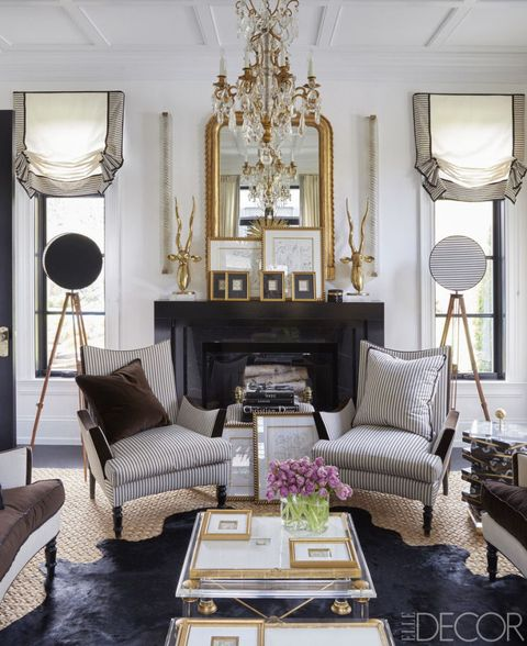 The living room armchairs, covered in a Rogers & Goffigon stripe, and cocktail tables are by Megan Winters Collection, the vintage chandelier is by Baccarat, the mirror was found in Paris, and the floor lamps are made from antique surveyor tripods; the linen wallcovering is by Ralph Lauren Home.
