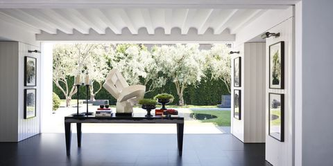 A 1960s French plaster sculpture sits on a table by Jean de Merry in the breezeway, which can be closed off with pocket doors; the flooring is basalt stone.