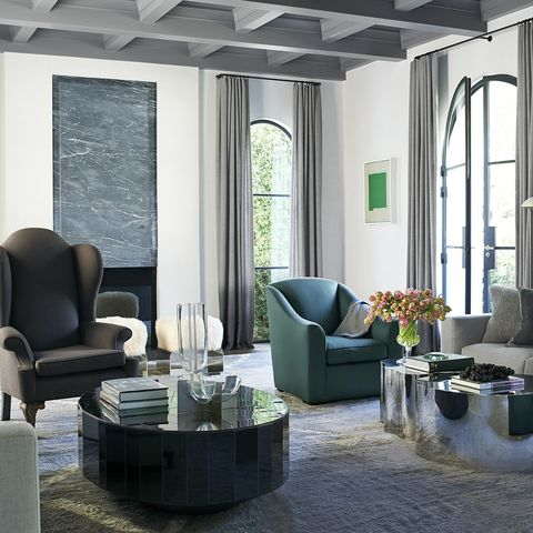In the living room of Mossimo Giannulli and Lori Loughlin's Beverly Hills house, which was designed by Jason and Katie Maine of Maine Design, sofas by Minotti flank a mirrored stainless steel cocktail table by Silas Seandel and a custom table by Sam Orlando Miller; the high-back armchair is by Blackman Cruz, the 1940s armchair is by Jean-Michel Frank, the sheepskin stools are by Azadeh Shladovsky, the fireplace surround is Bardiglio Venato marble, and the rug is custom made.