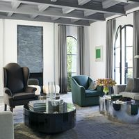 In the living room of Mossimo Giannulli and Lori Loughlin's Beverly Hills house, which was designed by Jason and Katie Maine of Maine Design, sofas by Minotti flank a mirrored stainless steel cocktail table by Silas Seandel and a custom table by Sam Orlando Miller&#x3B; the high-back armchair is by Blackman Cruz, the 1940s armchair is by Jean-Michel Frank, the sheepskin stools are by Azadeh Shladovsky, the fireplace surround is Bardiglio Venato marble, and the rug is custom made.