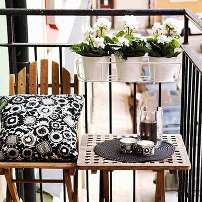A multitude of accessories turn this tiny balcony into the perfect spot to enjoy a cup of coffee or relax with a good book. A simple black and white color scheme keeps a lot of design elements from overwhelming a small space.