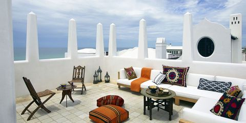 On the terrace, which overlooks the Gulf of Mexico, the bone-inlaid folding chairs, side table, and brass-topped cocktail table are Moroccan; the sofa pillows are covered in antique suzanis and the floor pillows in vintage kilims.