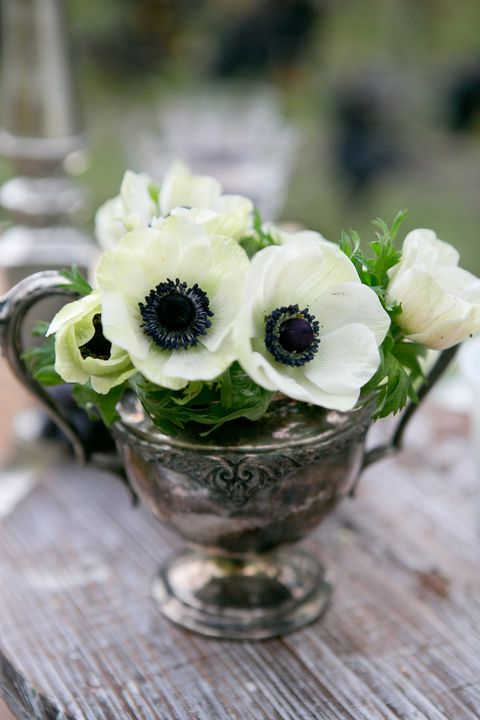 Sometimes you have to let the vessel be the star of the show. A metallic vase adds drama to this table when paired with understated blooms like delicate anemones.   <!--EndFragment-->