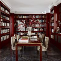 In the dining room-cum-library, chairs by Castillo are covered in a cut-velvet stripe by Robert Allen with backs in a Jim Thomson fabric. The lacquer-and-brass table is by Maison Jansen&#x3B; the walls and bookshelves are painted in Farrow &amp&#x3B; Ball's Rectory Red.