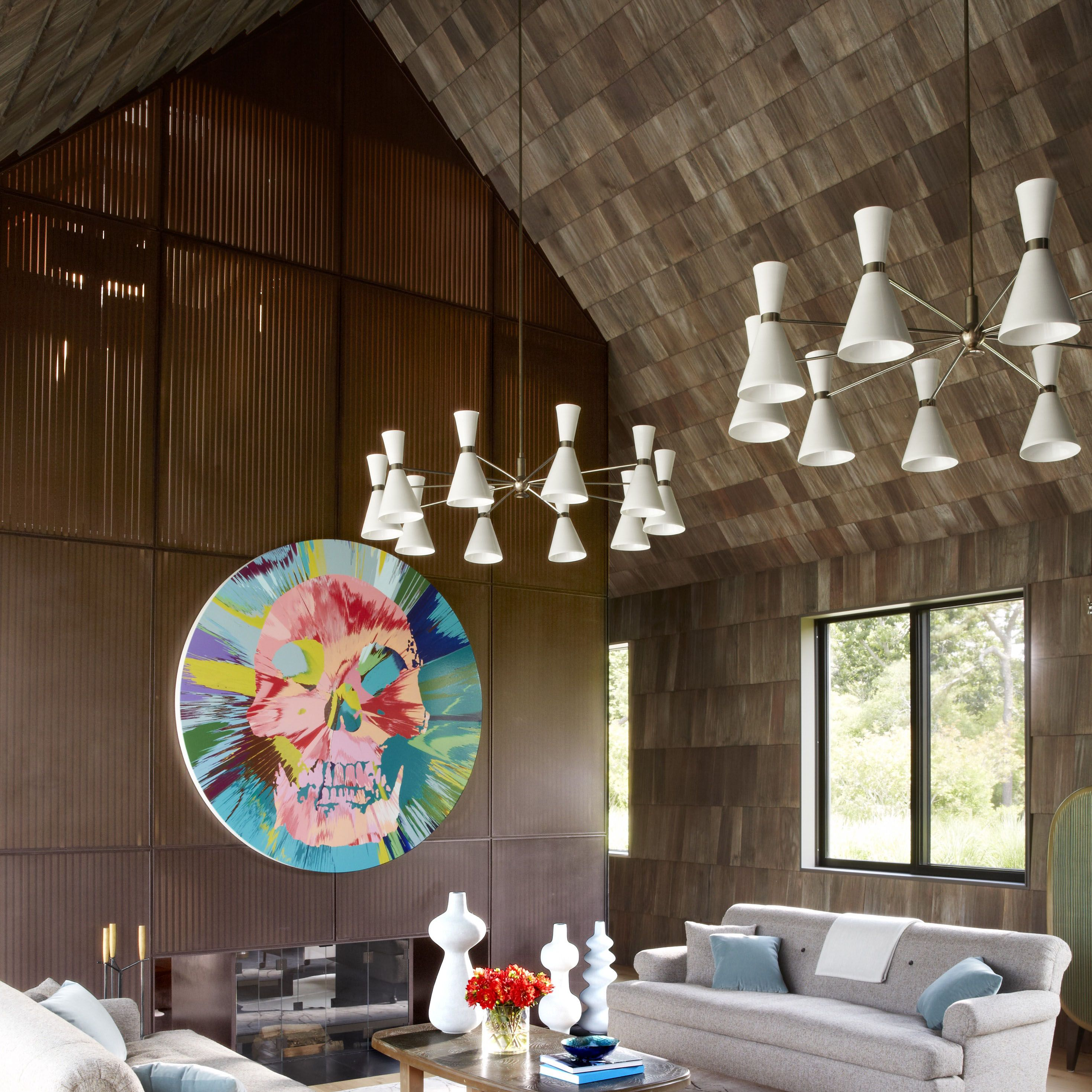The living room of a Long Island house designed by the architectural firm Bates Masi + Architects, with interior decoration by Damon Liss&#x3B; a pair of sofas by BDDW flanks a 1970s Belgian cocktail table from Van den Akker, the Stilnovo chandeliers and the Brazilian bench are from the 1950s, and a painting by Damien Hirst hangs on a wall of cedar slats.