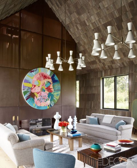 The living room of a Long Island house designed by the architectural firm Bates Masi + Architects, with interior decoration by Damon Liss; a pair of sofas by BDDW flanks a 1970s Belgian cocktail table from Van den Akker, the Stilnovo chandeliers and the Brazilian bench are from the 1950s, and a painting by Damien Hirst hangs on a wall of cedar slats.