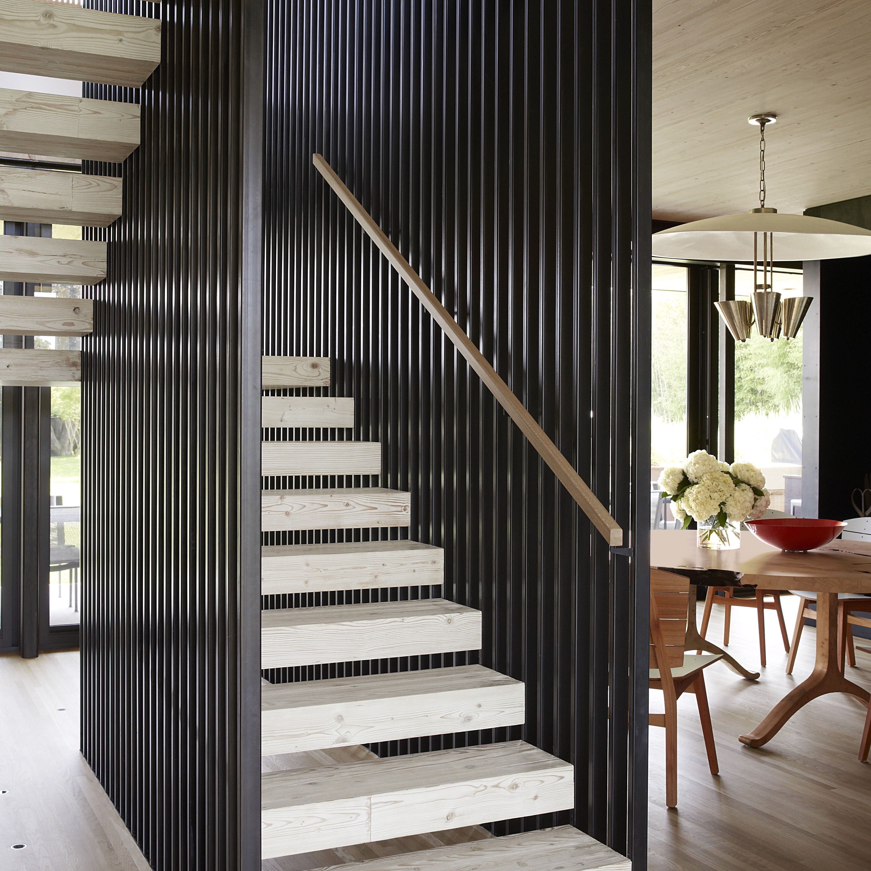 Chairs by Carlos Motta for Espasso surround a dining table by BDDW&#x3B; the 1950s American pendant originally hung in a Connecticut school, and the staircase is made of Douglas fir steps encased by cedar slats.