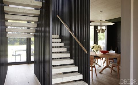 Chairs by Carlos Motta for Espasso surround a dining table by BDDW; the 1950s American pendant originally hung in a Connecticut school, and the staircase is made of Douglas fir steps encased by cedar slats.
