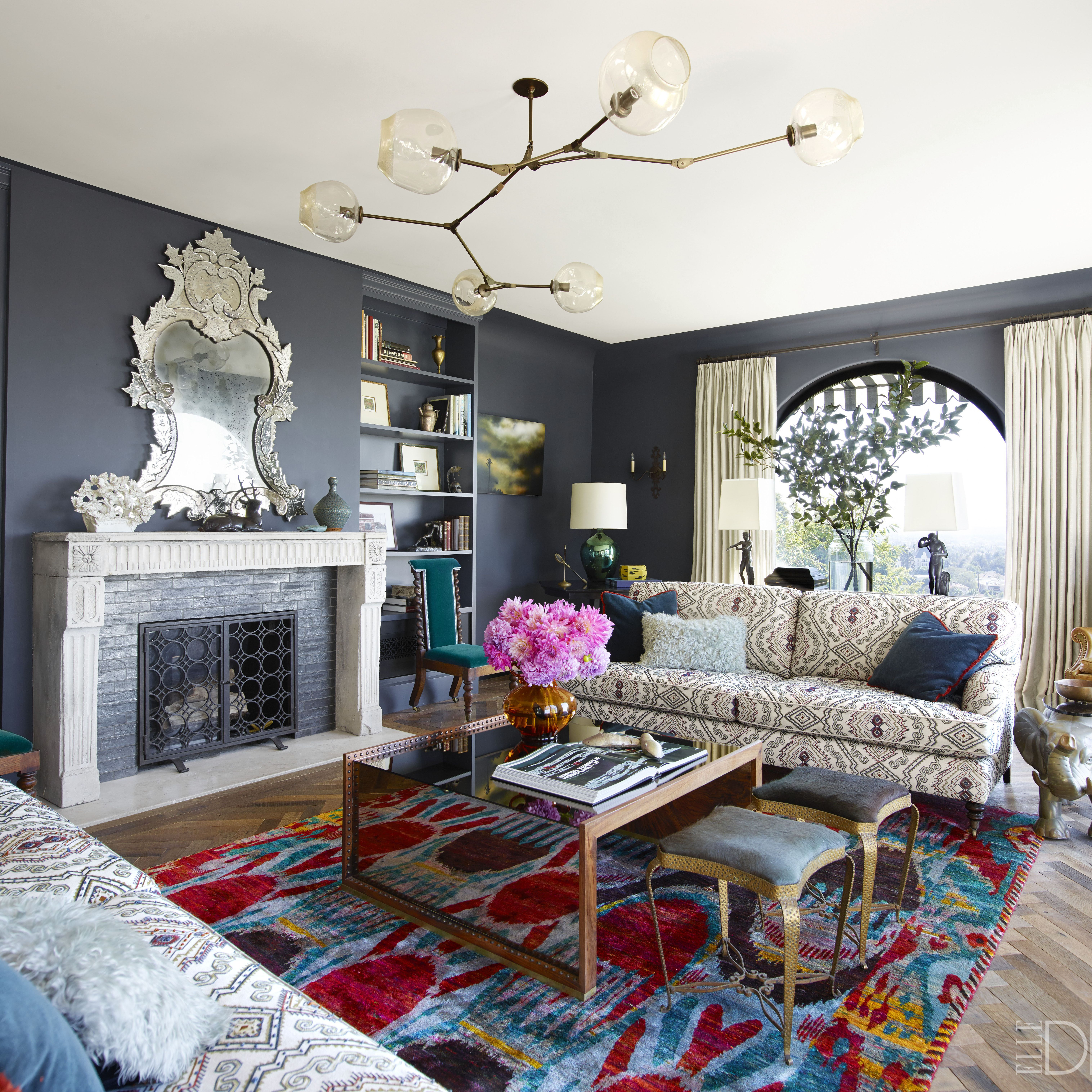 The living room of the Hollywood Hills home of Jamie Tarses and Paddy Aubrey, which was designed and renovated by Pamela Shamshiri of Commune Design. The sofas by George Smith are upholstered in an Oscar de la Renta for Lee Jofa fabric&#x3B; the cocktail table is a custom design, and the stools from Hollywood at Home and wing chair are vintage. The ceiling fixture is by Lindsey Adelman, the vintage mirror is from JF Chen, the fireplace is original to the house, and the walls are painted in Benjamin Moore's Hale Navy.