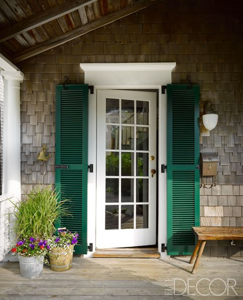 The front door's shutters are painted in Benjamin Moore's Chrome Green, and a vintage sign was made into a bench.