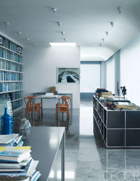 "<p>One wall of architect Felix Claus's Amsterdam study is lined with glass-fronted bookcases. A cabinet by USM faces a table surrounded by 1950s Hans Wegner Wishbone chairs&#x3B; the floor is Jura stone.</p><p><a href=""http://www.elledecor.com/design-decorate/house-interiors/g1179/blue-horizons/"">Look through photos of the rest of this home.</a></p>"