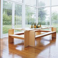 <p>In a Thomas Phifer-designed glass-and-steel weekend home in New York's Hudson Valley, Muriel Brandolini emphasized the verdant surroundings by keeping the breakfast-room furniture streamlined. The Martin Szekely birch-plywood table with attached benches is from Galerie Kreo.</p>