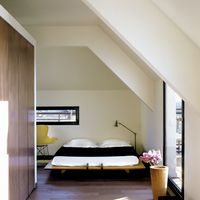 <p>Architect Sean McEvoy created an open floor plan for his rooftop apartment overlooking Paris's Right Bank. A cube structure, which houses the bathroom and closets, separates the bedroom from the main living area. The custom-made bed is dressed with a throw by Hermès.<span></span></p>