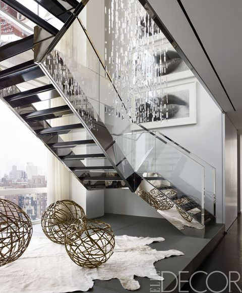 <p>A custom-made Swarovski-crystal light fixture hangs above a stainless steel-and-glass staircase; the bronze spheres are by Hervé Van der Straeten, and the photographs are by Sam Samore.</p>