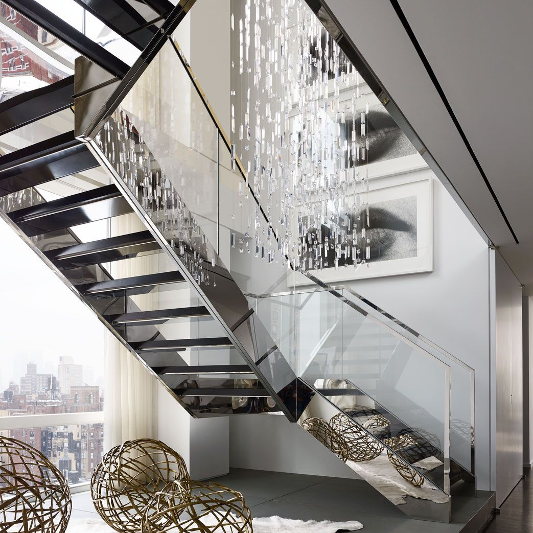 <p>A custom-made Swarovski-crystal light fixture hangs above a stainless steel-and-glass staircase&#x3B; the bronze spheres are by Hervé Van der Straeten, and the photographs are by Sam Samore.</p>