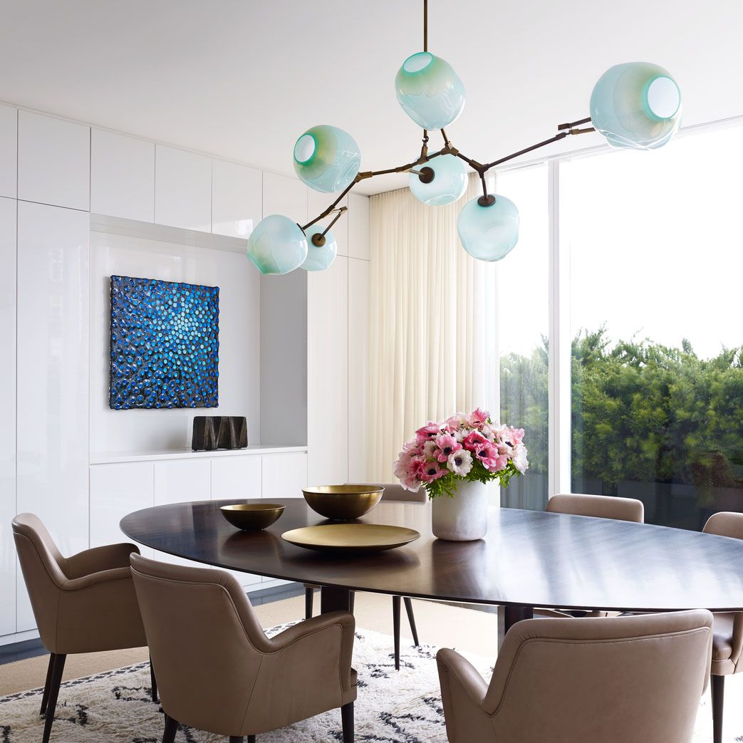 <p>A set of 1954 chairs by Osvaldo Borsani surrounds the custom-made dining table&#x3B; the light fixture is by Lindsey Adelman, and the painting is by Robert Melee.</p>