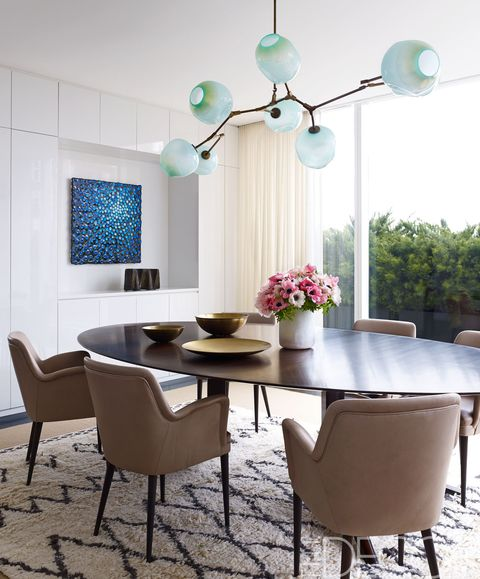 <p>A set of 1954 chairs by Osvaldo Borsani surrounds the custom-made dining table; the light fixture is by Lindsey Adelman, and the painting is by Robert Melee.</p>