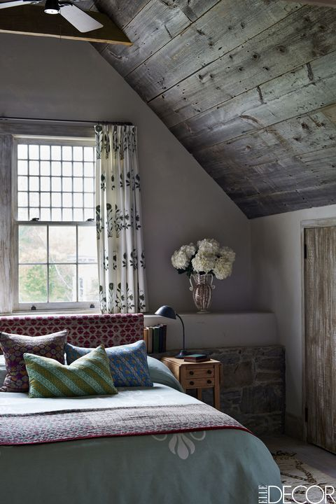 The headboard in the master bedroom is covered in a 19th-century Pakistani textile, and the spread was made in Venice.