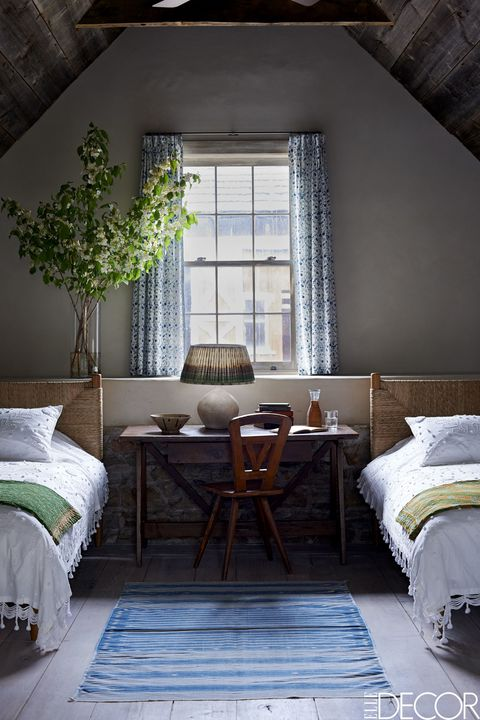 The custom beds in a guest room are dressed with spreads from Chelsea Textiles, the chair is from Avantgarden, and the late-17th-century table is French; the curtains are of a Les Indiennes cotton, and the rug is a vintage Indian dhurrie.
