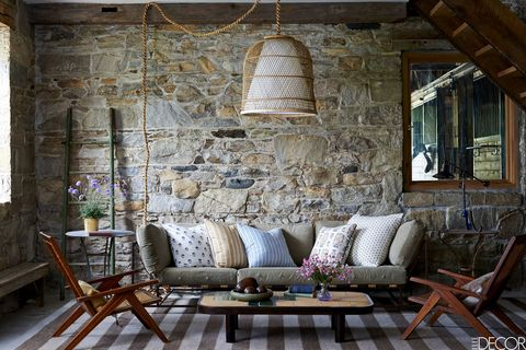 In the sitting area of Eric Hadar's carriage house in Bedford, New York, which was decorated by Virginia Tupker, a soft from Matter holds cushions from Les Indiennes and Nathan Turner, the chairs are by Pierre Jeanneret, and the cocktail table by Roger Capron is from Maison Gerard; the pendant light is by Roost, the ladder is from John Derian, the garden tables are French, and the wool rug is a custom design.