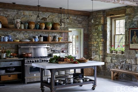 The kitchen island is made of a vintage marble slab on a steel base, the stove is by BlueStar, and the shelves are of reclaimed wood found on the farm; the pendant lights are from Rewire, and the floor is concrete.