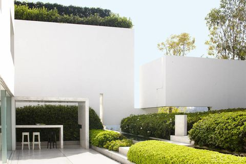 "The entry of the <a target=""_blank"" href=""http://www.elledecor.com/design-decorate/house-interiors/g1022/aragones-all-white-home/"">Mexico City home</a> of designer Miguel Ángel Aragonés and his wife, Ana, is lined with artworks by Jan Hendrix and highlights a view of the property's interior garden."