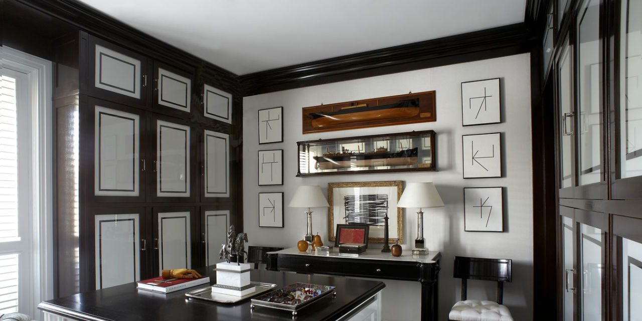 The cabinetry ebonized wood countertop and fabric covered wardrobe doors in the