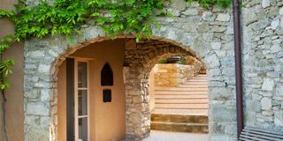 Property, Wall, Brick, Road surface, Real estate, Stone wall, Arch, Door, Brickwork, Concrete,