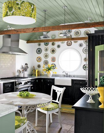 kitchen with green ceiling and plates on the wall around a round window