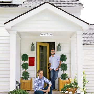 two men on the front porch of a white cottage