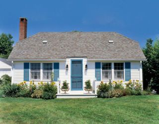 white house with blue shutters and door with lawn and flowers