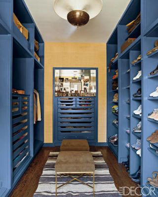 For his own Chicago apartment, decorator Nate Berkus applied his signature shock of color—in this case, bright blue—to the wardrobe, which features floor-to-ceiling shelving custom made in 1950 by the midcentury-modern architect Samuel Marx. The stools are by Paul McCobb, the rug is Moroccan, and the French light fixture is vintage. The back wall is covered in a grass cloth by Hinson & Co.