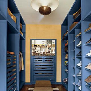 For his own Chicago apartment, decorator Nate Berkus applied his signature shock of color—in this case, bright blue—to the wardrobe, which features floor-to-ceiling shelving custom made in 1950 by the midcentury-modern architect Samuel Marx. The stools are by Paul McCobb, the rug is Moroccan, and the French light fixture is vintage. The back wall is covered in a grass cloth by Hinson &amp&#x3B; Co.