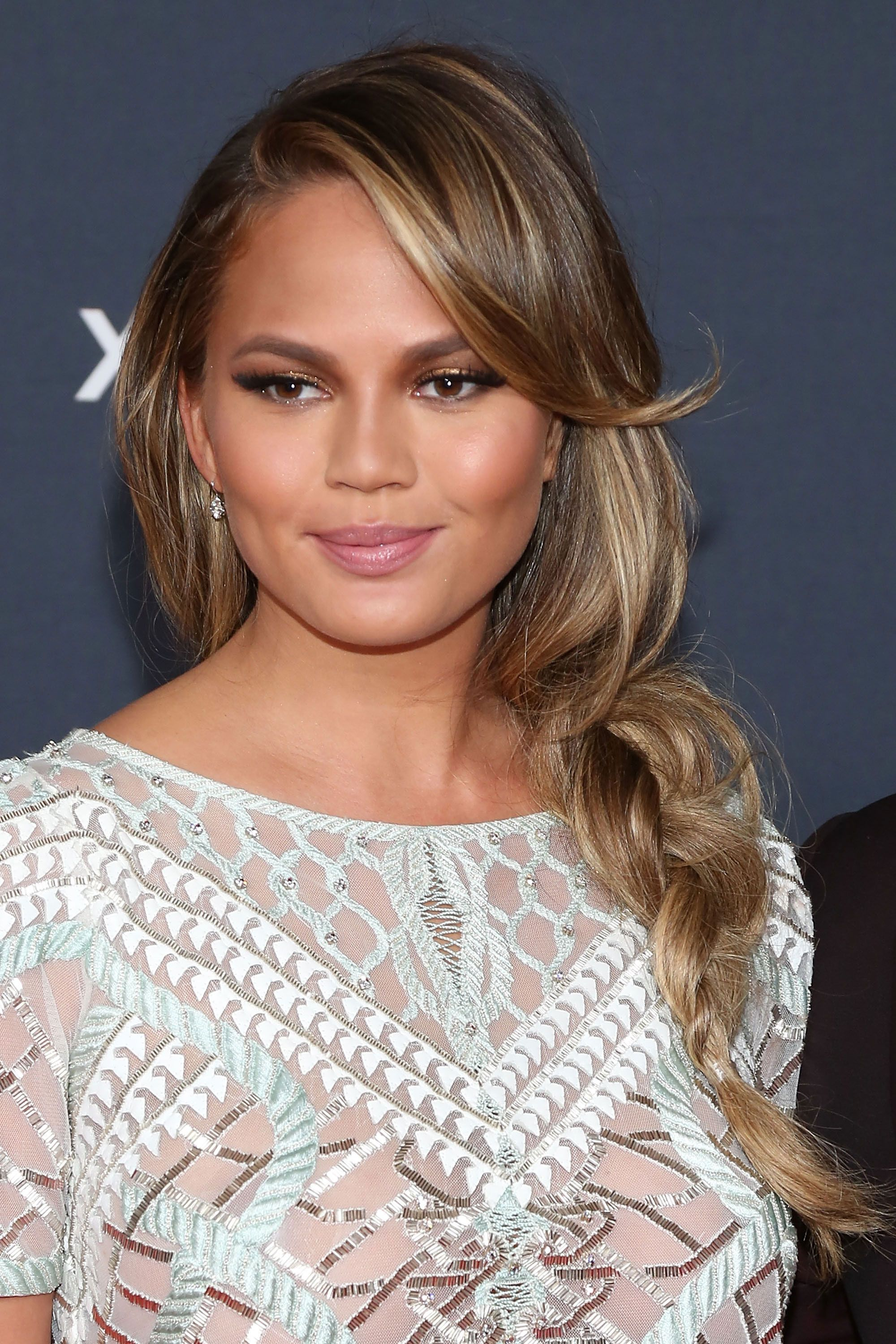 By pulling her loose waves into a voluminous side plait, Teigen emphasizes her caramel streaked strands.