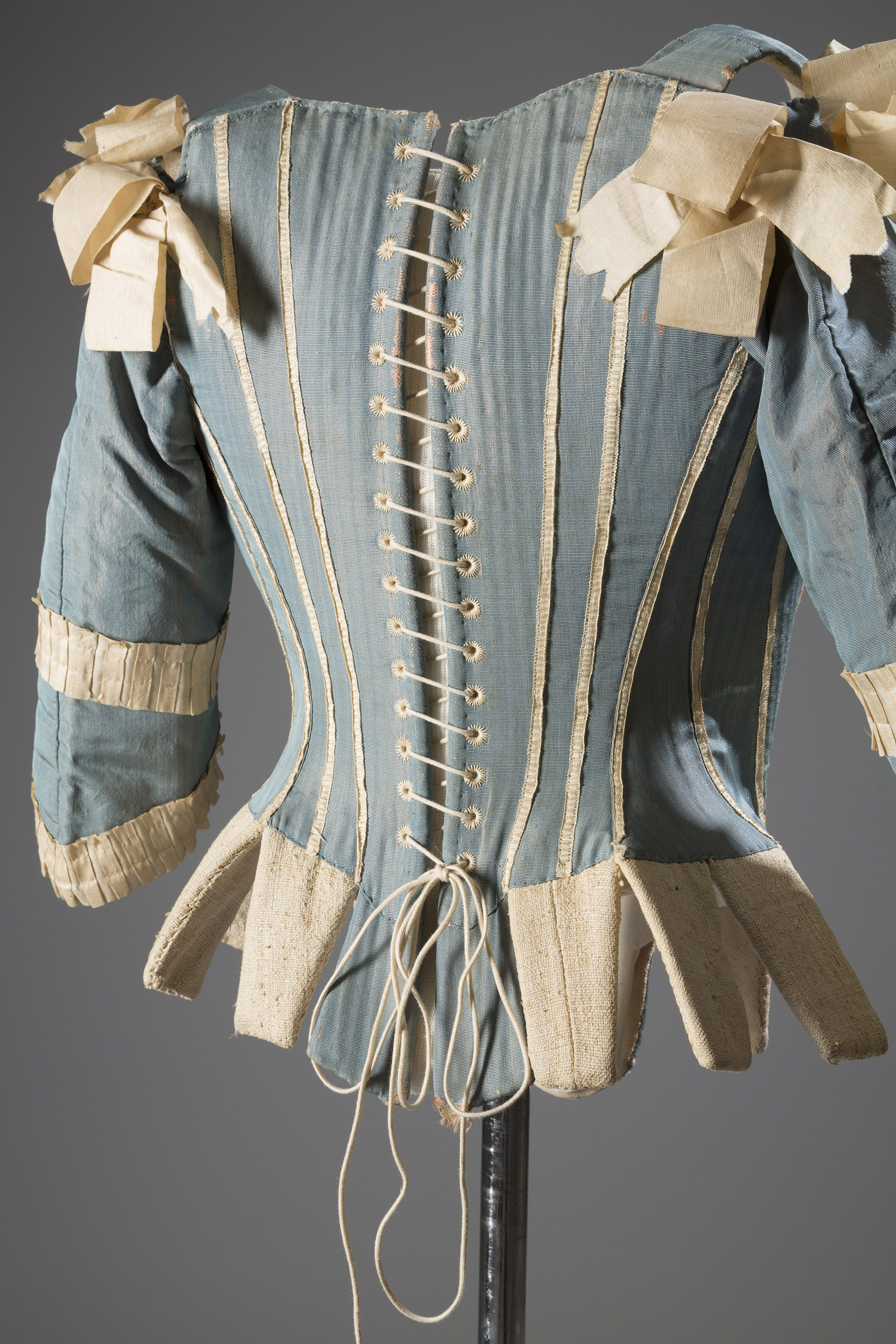 """Stays—otherwise known as whalebone corsets—were everyday wardrobe staples for """"proper"""" women of the eighteenth century. Yes, these undergarments don't look like the sexy bustier-corsets of today, but they were essential in molding&nbsp&#x3B;the ideal body form: a tiny waist and pushed-up breasts. As Colleen Hill notes&nbsp&#x3B;in <em><a href=""""http://www.amazon.com/Exposed-History-Lingerie-Colleen-Hill/dp/0300208863"""">Exposed: A History of Lingerie</a></em>, the French ceremonial ritual of the <em>toilette</em>, a morning routine of&nbsp&#x3B;undressing and dressing in front of the court, involved putting on a stay. Women performing the <em>toilette</em> would linger on the undergarments, hinting at the sexual intimacy and voyeurism involved.<em>Corset (Stays)/Silk, Silk Ribbon, Whalebone, ca.1770, Possibly Europe</em><!--EndFragment--><!--EndFragment-->"""