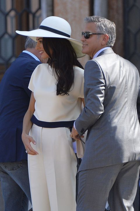 Amal has lived in London for a long time, so it's not surprising that she can wear a hat with aplomb. She seems to favor floppy, wide-brimmed hats–to protect her skin, perhaps?–but they complement her long locks beautifully.