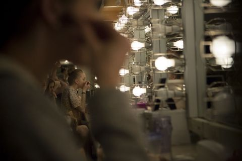 Corps de Ballet dancers apply their makeup backstage.