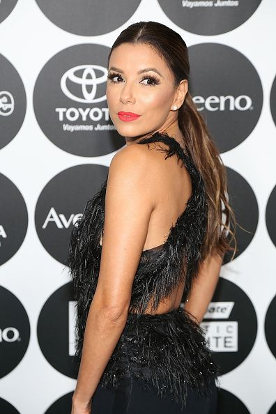 Longoria's coral lip and mega-thick lashes offset her fringed dress.
