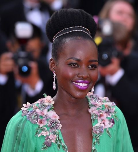 Nyong'o purple lips echoed the whimsical girlyness of her accessorized bun.