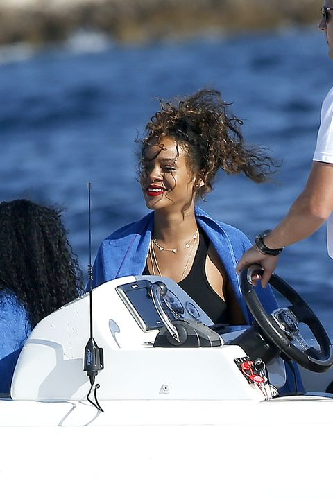 **USA ONLY** Antibes, France - Rihanna brings her effortless beauty to shore in Antibes, France with a couple of girl friends to visit the Hotel Du Cap-Eden-Roc.  The singer wore a black crop top with a white button up skirt and had her ankle strap heels in hand as she made her way up to the hotel.  Rihanna has been enjoying her summer vacation cruising along the Mediterranean Sea.