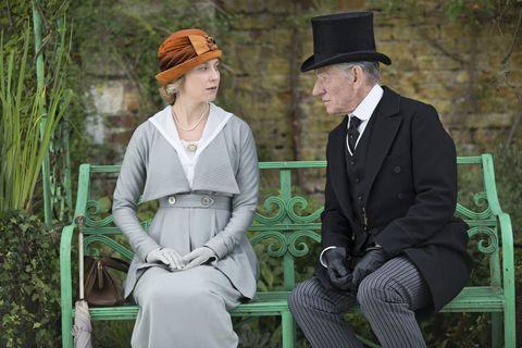 Hat, Sitting, Outerwear, Coat, Formal wear, Headgear, Dress, Fashion accessory, Suit trousers, Sun hat,