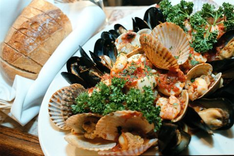 """<p>The most essential part? The food, of course! """"My family does something called The Feast of the Seven Fishes,"""" says D'Argenzio. """"It's these seven dishes from shellfish and regular fish. It's amazing but it's an incredibly heavy lift on a host. You <em>can</em> do it potluck style, which is fun. I like to re-create the idea of the Seven Fishes especially for a more celebratory, holiday vibe with a Frutti di Mare pasta dish, which has everything from the sea—shrimp, calamari, mussels, clams, a meaty white fish.""""</p>"""