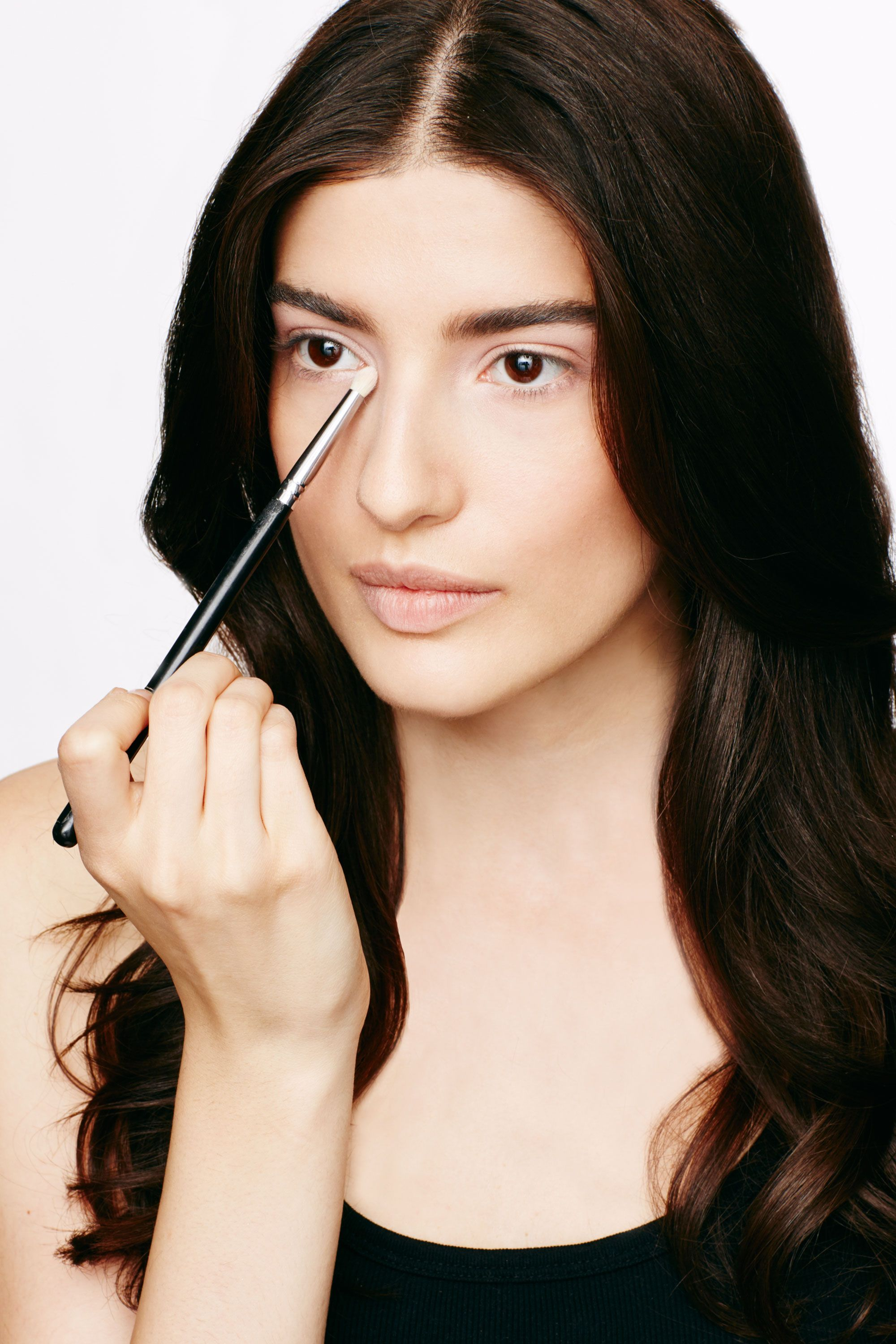 <p>With a small eyeshadow brush, sweep the light peach shade across the lid up to the crease and into the inner corner. The neutral shade will anchor bolder layers, Lledo says.</p>