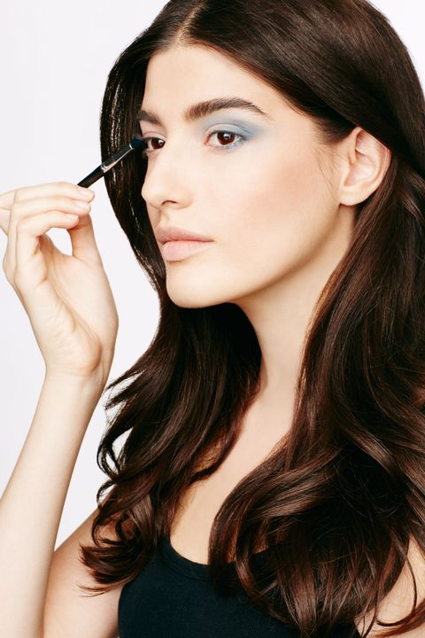 <p>With a fluffy eyeshadow brush (which helps diffuse a bold color), apply the blue shade along and slightly above the crease, extending the line out past the outer corner. Next, trace the brush outward along the bottom lash line and back over the lid, stopping midway above the pupil.</p>