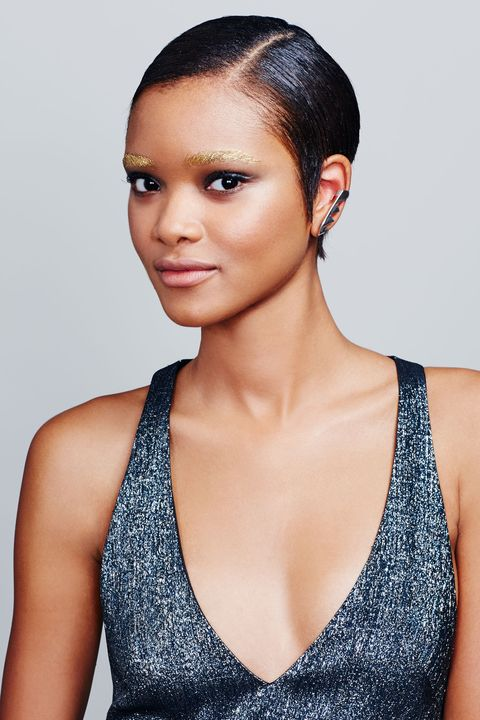 """<p>""""Metallics suit every skin tone,"""" says of Oquendo of the universally flattering color seen on the eclectic cast at shows like <a href=""""http://www.elle.com/beauty/makeup-skin-care/how-to/g27002/best-lipstick-looks-spring-2016-shows/?slide=1"""" target=""""_blank"""">Prada</a> this season. Going for the gold above your eyes, however, requires a definitive brow shape. Fill in your arches with a pencil (like <a href=""""http://www.amazon.com/Maybelline-New-York-Eyestudio-Precise/dp/B00PFCSBXG/ref=sr_1_1?ie=UTF8&qid=1449129552&sr=8-1&keywords=maybelline+brow+precise"""" target=""""_blank"""">Maybelline New York Brow Precise</a>) a shade lighter than your hair color. Then, coat brows with a long-lasting gel formula (such as <a href=""""http://www.amazon.com/Maybelline-EyeStudio-Color-Tattoo-Eyeshadow/dp/B00GWBZJ3Y/ref=sr_1_2?ie=UTF8&qid=1449129725&sr=8-2&keywords=maybelline+color+tattoo+gold+rush"""" target=""""_blank"""">Maybelline New York Eye Studio Color Tattoo Metal 24HR Cream Gel Shadow in Gold Rush</a>) using a stiff, flat brush. """"This cream shadow is so pigmented and bright that you only have to pop on a quick layer,"""" says the pro. To balance high-shine brows, smudge a black liner over lids and a brown pencil along your lower lash lines. """"Keeping the rest of the eye undone is what makes high-octane, gilded arches look modern,"""" explains Oquendo of the foiled finish.</p><p><em>Dress: Camilla and Marc; Ear Cuff: Karimi</em></p>"""