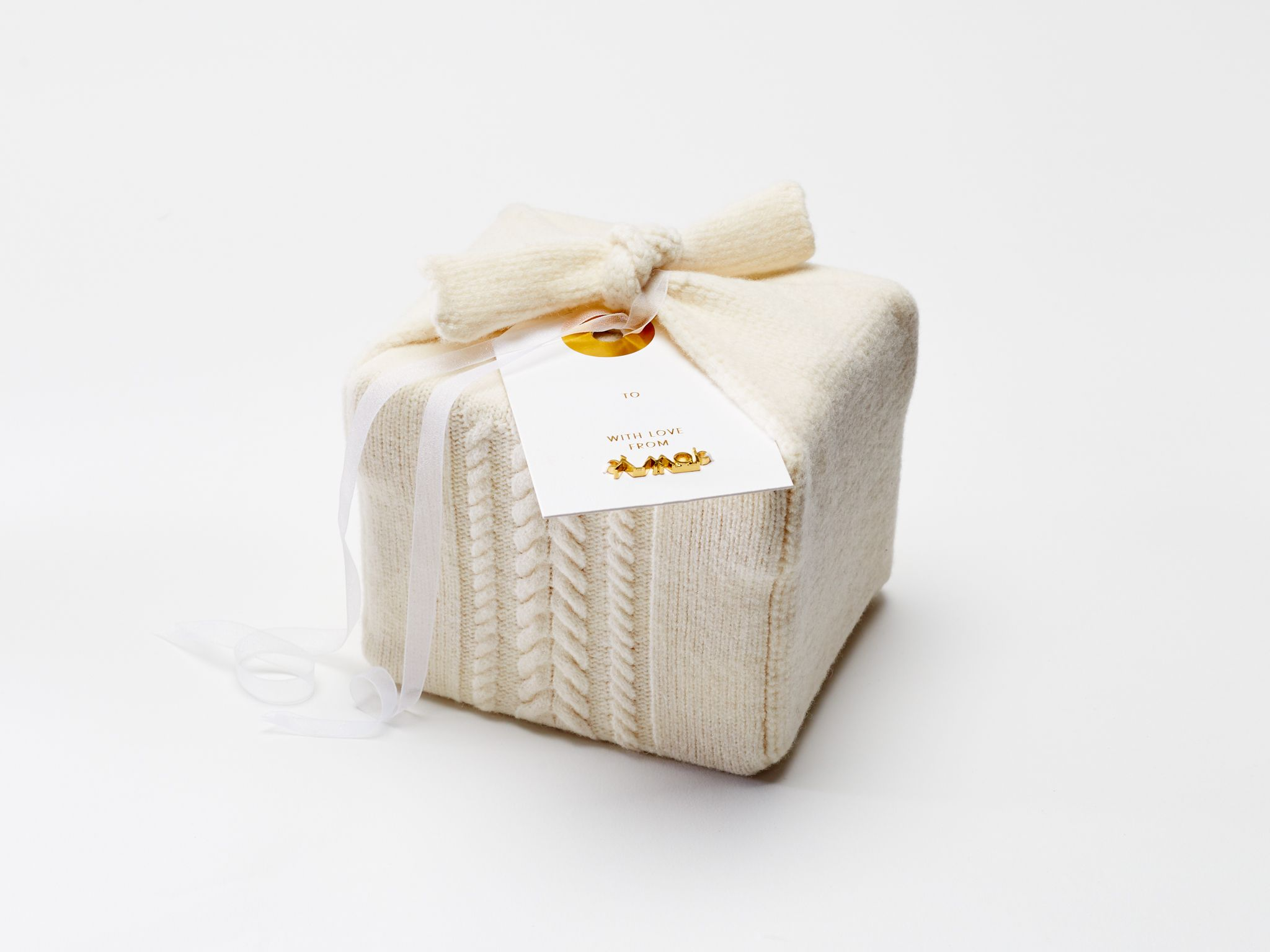 "<p>""Knitted with Italian wool from our Fall 2015 collection, we created a gift wrap with The Knit Resource center that warms up a cold New York winter and can be used again and again."" <em>—  Alejandra Alonso, <em>A Moi designer</em></em></p>"