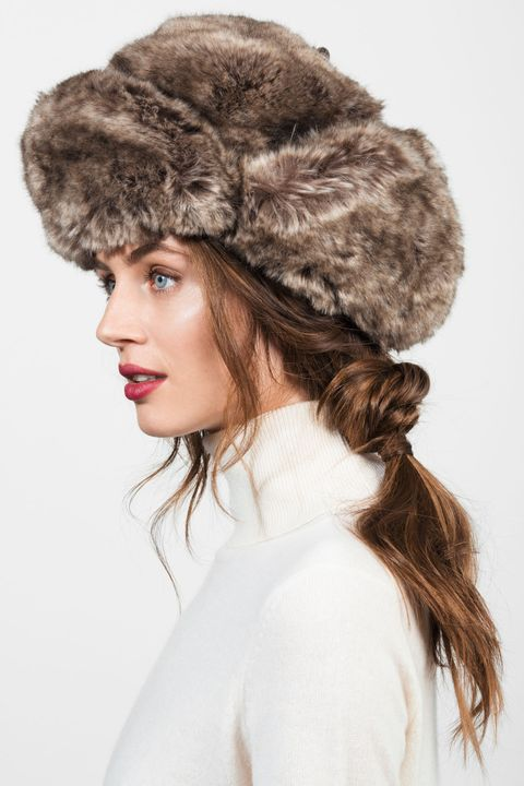 """<p>A pretty knotted ponytail with soft, face-framing pieces does the trick of adding femininity to a heavy hunting hat. Separate your hair into three sections like you would for a classic braid, then tie the two on the outside together in a knot in front of the middle section. Wrap them around and knot them again in the back, and finish by securing the whole ponytail with an elastic. </p><p><strong>Albertus Swanepoel</strong> Bambi hat, $250, <a href=""""http://albertusswanepoel.com/shop/white-trapper"""" target=""""_blank"""">albertusswanepoel.com</a>; <strong>White + Warren</strong> Essential Cashmere Turtleneck, $198, <a href=""""http://www.whiteandwarren.com/essential-cashmere-turtleneck-36?mkwid=s4gbnp9xg&crid=86238602065&mp_kw=&mp_mt=&pdv=c&gclid=CK7CoJWfk8oCFYQYHwodXCEH1Q"""" target=""""_blank"""">whiteandwarren.com</a>.</p>"""