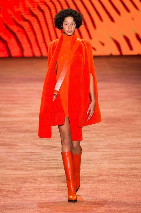 Red, Outerwear, Orange, Fashion show, Runway, Fashion, Fashion model, Costume design, High heels, Boot,