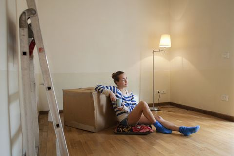 woman sitting on floor in empty house